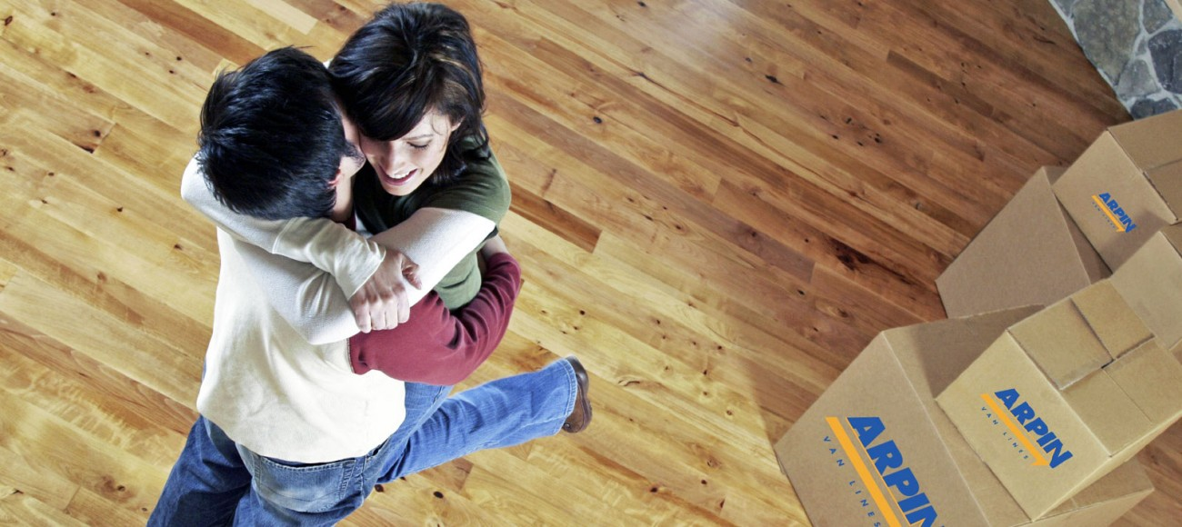 Couple hugging by moving boxes
