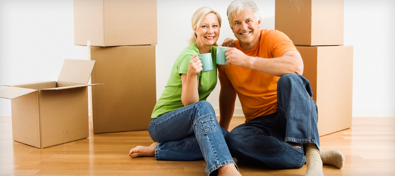 Smiling couple sitting in front of moving boxes