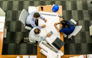workers around a table with white roll of paper unrolled
